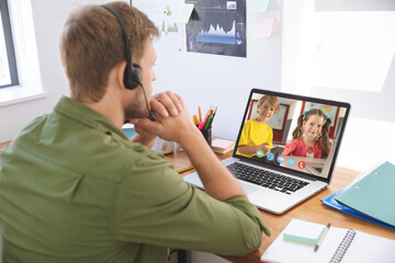Male teacher wearing headphones having a video conference with male and female students on laptop at