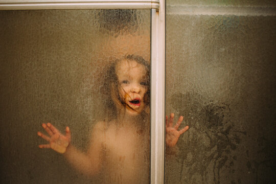 Portrait of girl in shower seen through glass