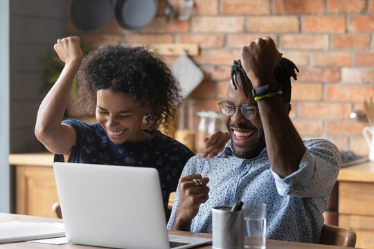 Close up excited African American couple celebrating success, using laptop, overjoyed wife and husband received good news in email, online lottery win or approved mortgage loan, showing yes gesture