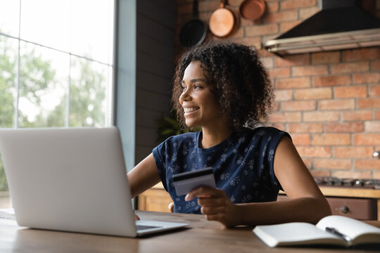 Close up smiling dreamy African American woman holding credit card, sitting at table with laptop, shopping online, making internet payment, dreaming about new opportunity, investment and insurance