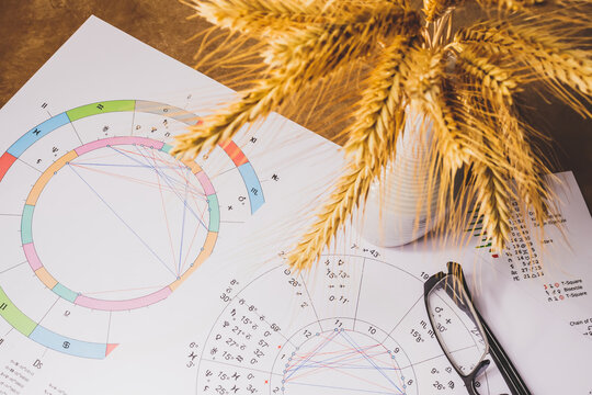 The workplace of an astrologer, magician and sorcerer of our time. Hobby during the coronavirus pandemic. Astrological charts and tables built with the help of modern gadgets, laid out on the table.