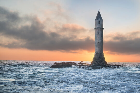 Low angle view of lighthouse amidst sea against cloudy sky during sunset
