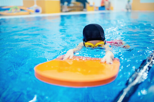Happy little kid girl learning to swim with pool board with coach woman