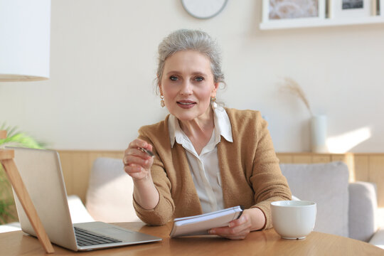 Portait of smiling beautiful middle aged woman looking at camera, making video call, job interview or online dating.
