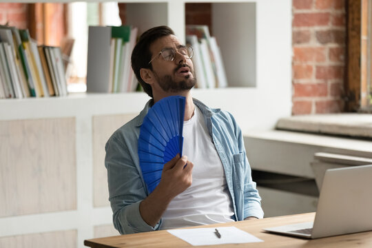 Unwell young Caucasian male employee sit on desk work on computer wave with hand fan. Overheated man worker use waver suffer from heatstroke in office, struggle with no AC at workplace.