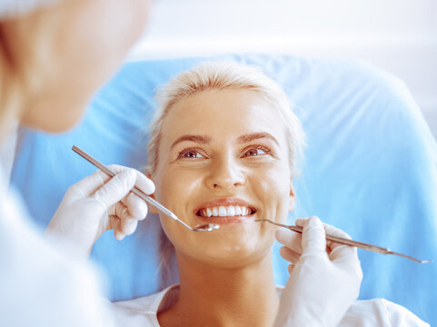 Smiling blonde woman examined by dentist at dental clinic. Healthy teeth in medicine concept