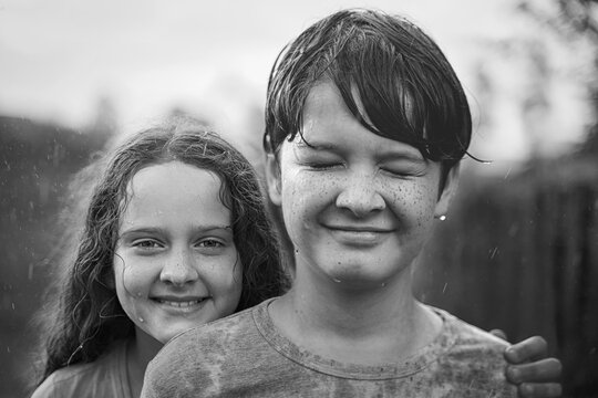 Cute children embacing and playing in the rain