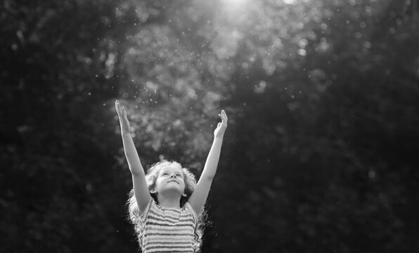 Cute little girl stretches her hand to catch sun rays.