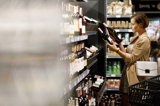 young girl are shopping at a supermarket. girl are choosing drinks. Alcohol drinks