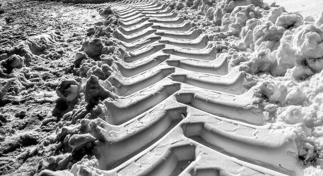 Wide deepened tracks from tractor tires in fresh soft white snow with high contrast