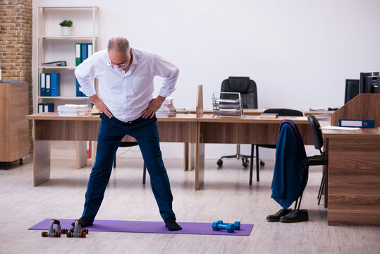 Old businessman employee doing sport exercises in the office