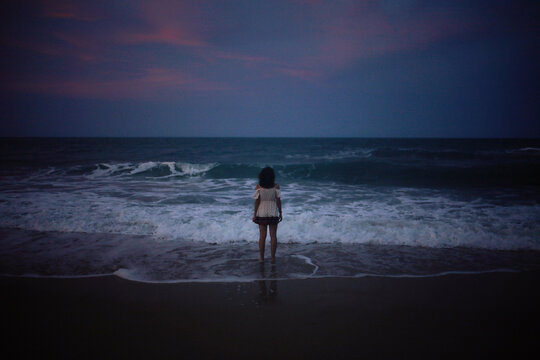 Rear view of woman standing in sea against sky at dusk
