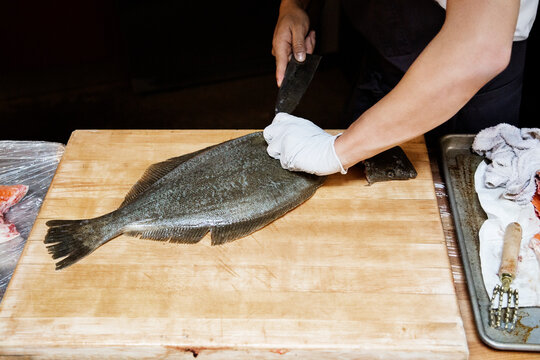 Cropped image of chef cutting fish on cutting board