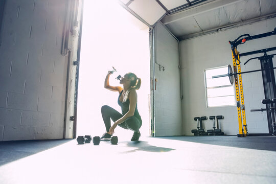 Woman drinking water while crouching in brightly lit gym