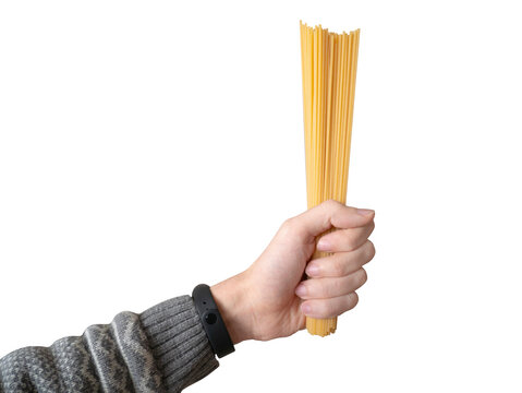 Hand holds spaghetti isolated on white background. Raw pasta. Typical Italian food.