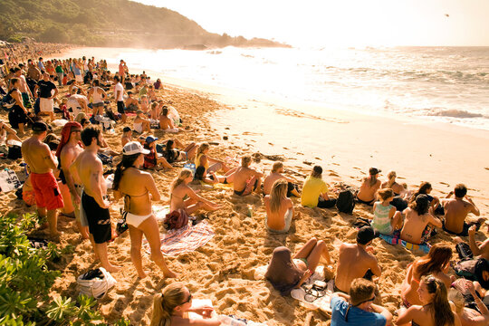 large crowd of people watch the Eddie Aikau surfing competition at Waimea Bay
