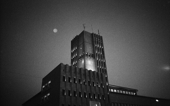 Grayscale shot of an illuminated modern building and a moon in the clear sku