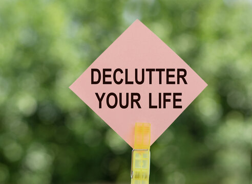 DECLUTTER YOUR LIFE - text on pink note paper on green background.