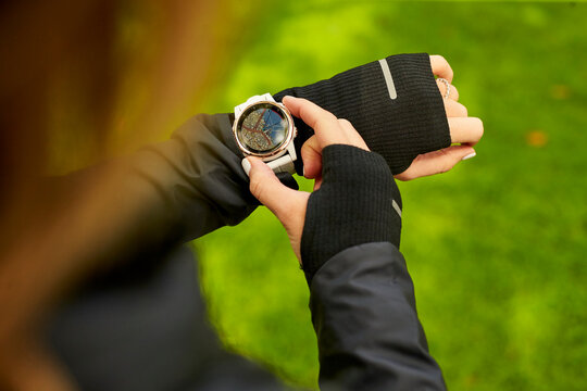 An overhead shot of a woman looking at a map on her fitness watch.