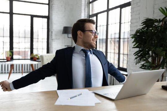Young male CEO or employer sit at table at workplace stretch after long hours computer work. Caucasian businessman in suit feel excited relieved after job finish, relax rest at desk in office.