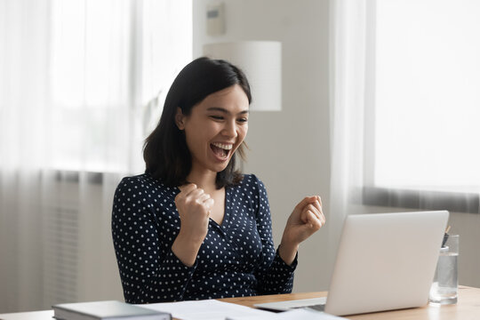 Excited young vietnamese woman look at laptop pc screen in delight receiving good news being accepted admitted to college university. Overjoyed asian lady office worker get reward promotion by email