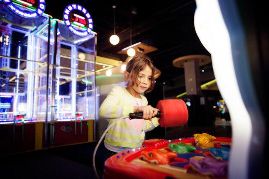 Girl playing game at amusement arcade