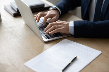 Close up of successful businessman sit at desk in office work distant with paperwork type on laptop gadget. Male CEO or director message consult business customer or partner on computer online.