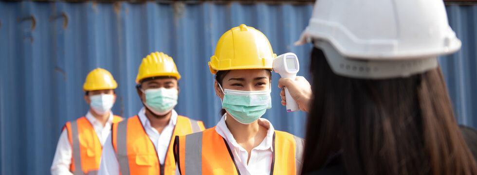 The supervisor checks the day of the body temperature of the employee before entering the workplace by a medical meter to prevent communicable diseases.