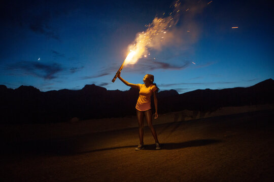 Smiling woman burning fireworks on mountain against sky at dusk