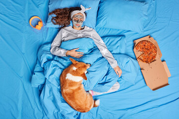 Pleased brunette young woman applies clay mask on face undergoes beauty mask before sleeping looks at her dog pose on comfortable bed under soft blanket awake in cozy bedroom. Wake up in morning