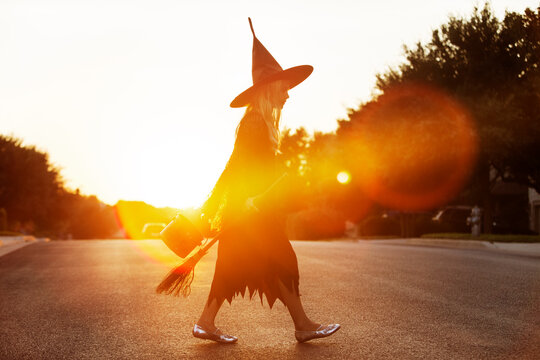 Girl dressed in witch costume walking on road during sunset