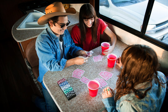 High angel view of friends playing cards at table while travelling in camper van