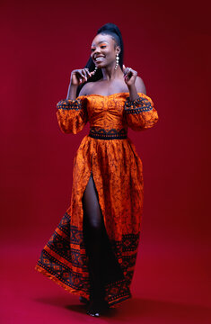 beautiful happy african woman in traditional dress dancing on red background, studio shot