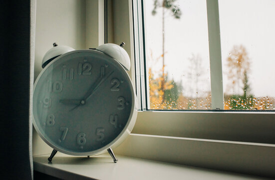 a large alarm clock on a window ledge with rain on the window