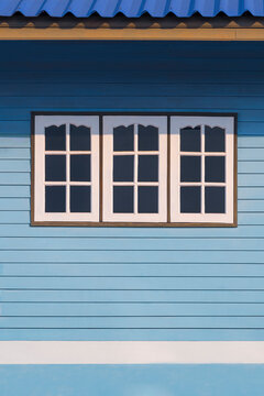 Sunlight on surface of 3 white windows on blue wooden wall of the old vintage house in vertical frame