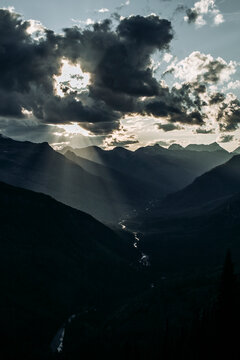 Sun bursts through clouds in mountain valley, Glacier National Park