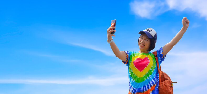 Asian female traveler in colorful casual style using smartphone taking selfie with smiling cheerfully and raise her hand against white clouds and blue sky background in enjoying weekend vacation