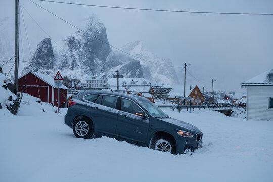 Tourist rental car stuck in ditch on side of road on snow covered winter roadway, near Reine, Lofoten Islands, Norway