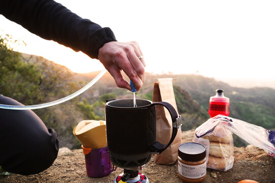 camper making coffee in mountains at sunrise