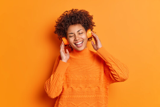 Pleased Afro American woman enjoys pleasant song via stereo headphones smiles broadly keeps eyes closed has happy expression wears casual sweater isolated over orange background. Lifestyle leisure