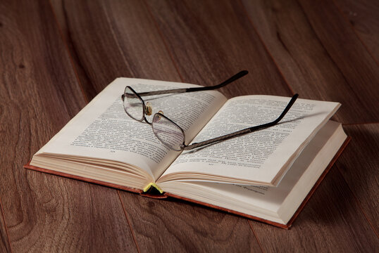 The opened book with glasses on it on wooden background