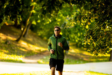 Athletic young man running while doing workout in sunny green park