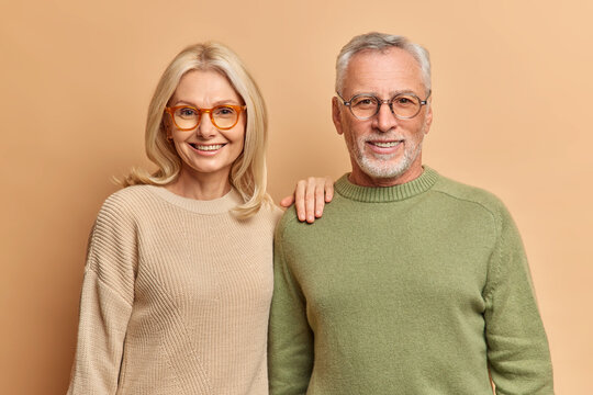 Half length shot of pleased middle aged woman and man smile pleasantly wear jumpers and spectacles for good vision look directly at camera isolated over brown background. Daily lifestyle concept