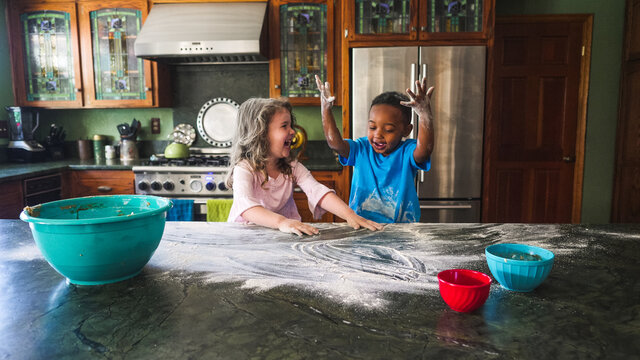 Girl laughing at boy while they make a mess in the kitchen