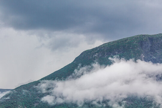 Fog mist clouds cliffs on mountain norwegian landscape Jotunheimen Norway.