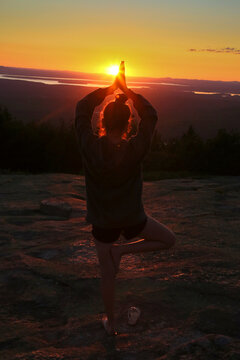 A teenage girl does a yoga pose while facing the sun as it sets over t