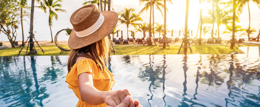Young couple traveler relaxing and enjoying the sunset by a tropical resort pool while traveling for summer vacation