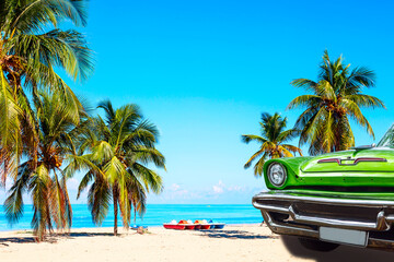 The tropical beach of Varadero in Cuba with green american classic car, sailboats and palm trees on...