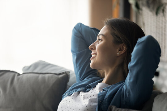Captured by dreams. Happy serene millennial woman relax on sofa with hands over head look away dream imagine. Calm peaceful young lady sit in soft pillows rest alone remember good moments. Copy space