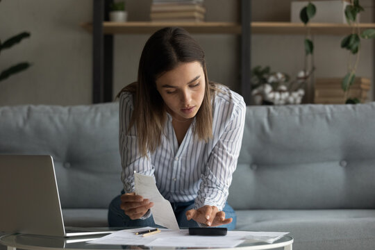 Young woman wife work with bills invoices at home office plan family budget count monthly expenses check receipts apply sums to get total cost. Busy millennial female focused on accounting paperwork